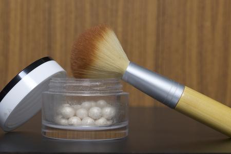Foto de Golden highlighter in the form of balls in an open jar. Next to it is a cosmetic brush for applying it. - Imagen libre de derechos