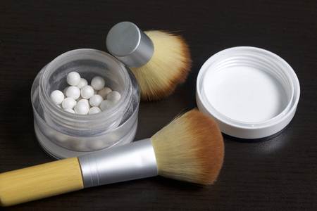 Foto de Pearl highlighter in the form of balls in an open jar. Close to the brush for applying cosmetics. On a dark background, view from above. - Imagen libre de derechos