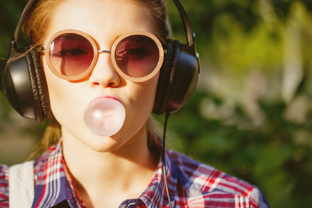 Foto de Young hipster girl listening to music on headphones in a summer park. Portrait close-up with chewing gum. Warm toning. The concept of cheerful youth. - Imagen libre de derechos