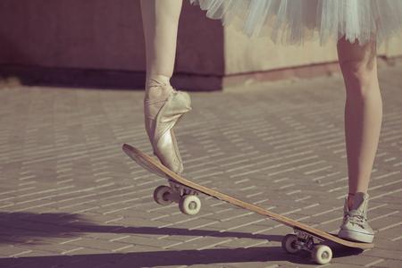 Foto de The legs of a ballerina on a skateboard. Feet shod in sneakers and ballet shoes. Modern fashion. Photo closeup. - Imagen libre de derechos