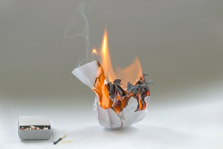 Foto de Crumpled paper burning in fire and matchbox . Burning white paper ball in flame and box of matches. - Imagen libre de derechos