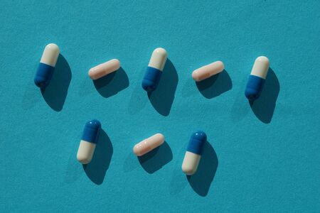 Pharmaceutical drug - blue and white pills on blue background.