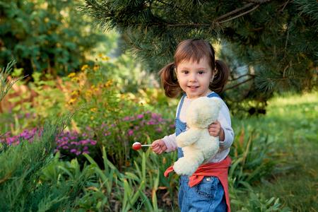 Photo pour little happy girl with two ponytails. beautiful little girl eats candy - image libre de droit