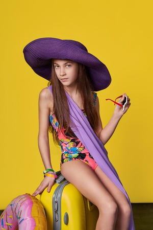 Photo for Attractive girl teenager 11 years in swimsuit, hat, holds sunglasses in his hand. Concept summer, travel. Portrait cute young beauty woman on a bright yellow background studio. - Royalty Free Image