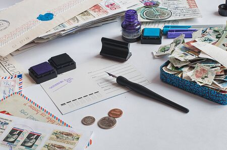 Photo for Postcrossing still life. Unwritten postcard in the center, hand writing with a fountain pen, ink, stamps, coins around. - Royalty Free Image
