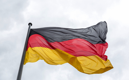 Foto de The national flag of the Federal Republic of Germany has evolved in the wind against the sky - Imagen libre de derechos