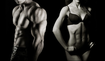 Foto de Bodybuilding  Strong man and a woman posing on a black background - Imagen libre de derechos