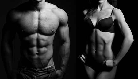 Foto de Bodybuilding. Strong man and a woman posing on a black background - Imagen libre de derechos