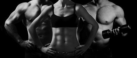 Photo pour Bodybuilding. Strong man and a woman posing on a black background - image libre de droit