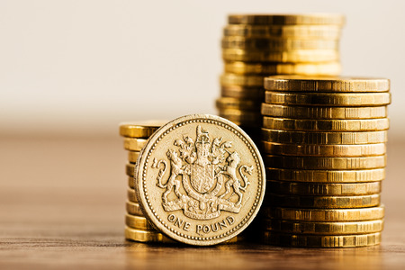 Photo for pound GBP coin and gold money on the desk - Royalty Free Image