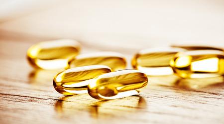 Photo pour Fish oil omega 3 gel capsules  on wooden background - image libre de droit