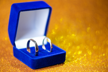 Photo pour gold wedding rings in the blue jewelery box. Glitter background - image libre de droit