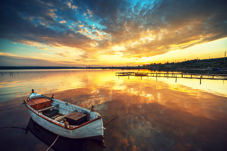 Photo pour Boat on lake with a reflection in the water at sunset - image libre de droit