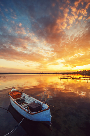 Foto de Boat on lake with a reflection in the water at sunset - Imagen libre de derechos