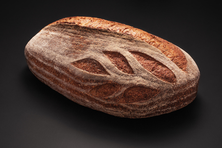 Photo pour Whole wheat sourdough freshly baked bread on black background. - image libre de droit