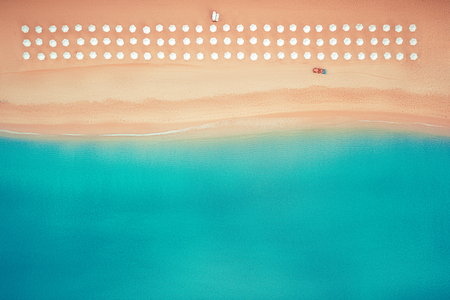 Foto de Aerial top view on the beach. Umbrellas, sand and sea waves - Imagen libre de derechos