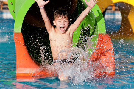 Photo for Boy has into pool after going down water slide during summer - Royalty Free Image