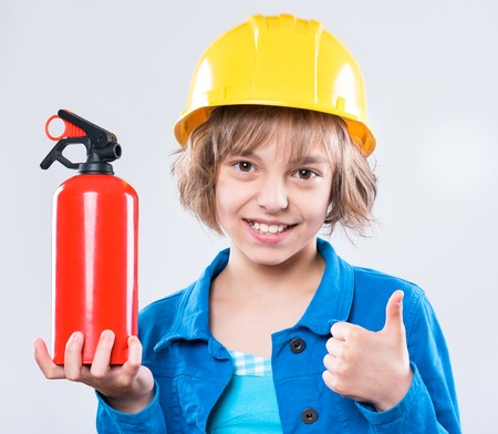 Photo pour Emotional portrait of attractive caucasian girl wearing safety yellow hard hat. Beautiful happy child holding a fire extinguisher, showing thumb up gesture and looking at camera. - image libre de droit