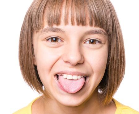 Foto de Nice girl showing her tongue. Child puts out tongue - close up. - Imagen libre de derechos