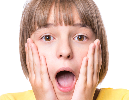 Foto de Emotional portrait of excited little girl. Funny cute surprised child 10 year old with mouth open in amazement. Portrait of shocked teenager, isolated on white background. - Imagen libre de derechos