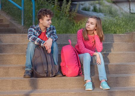 Photo pour Unhappy teenage boy and girl sitting on stairs outdoors. Sister and brother teens with backpacks. Sad children do not want to go to school. Childhood and Back to school concept. - image libre de droit
