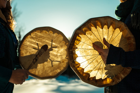 Foto de Women holding and playing their sacred drums outdoors in the wintertime - Imagen libre de derechos