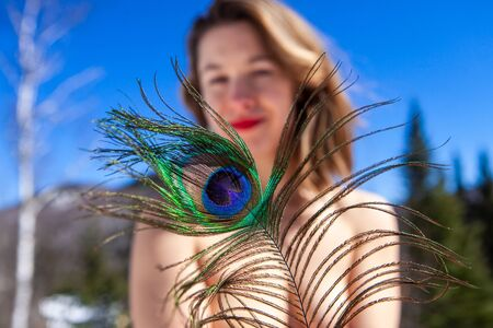 Photo for A close-up view of a peacock tail, held be a young Caucasian lady standing topless against a scenic mountain landscape with blue sky. Nude woman in mountains. - Royalty Free Image