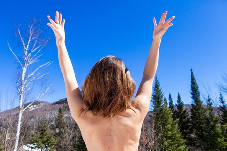 Photo for A nude Caucasian lady is viewed from behind doing relaxing arm stretches in a quiet mountain spot. Meditation and relaxation in a natural setting. - Royalty Free Image