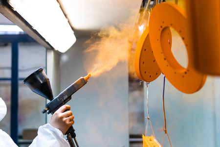 Photo pour Powder coating of metal parts. A woman in a protective suit sprays powder paint from a gun on metal products - image libre de droit