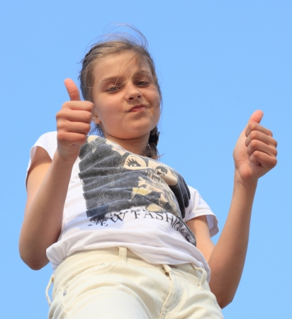 blonde girl in bright clothing keeps hands in fists raised thumb up against the sky