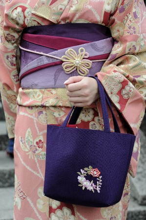 Kyoto, Japan - November 4: Geisha wearing a kimono with red munsuko and red obi.This is a traditional Japanese dress. Kyoto is the capital of the geisha world. November 4, 2014 Kyoto, Japan