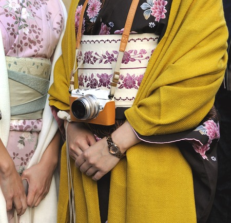 Kyoto; Japan - November 3, 2014: Two Geishas wearing kimonos; one of them with a small digital camera. The kimono is a traditional Japanese dress. Kyoto is also known as the capital of the Geisha world. November 3; 2014 Kyoto; Japan