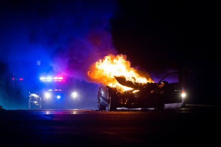Foto de Car on fire at night with police lights in background at night - Imagen libre de derechos