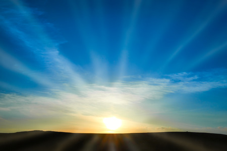 Foto de Sun rising above the land on blue sky. Nature background with sunny beams - Imagen libre de derechos