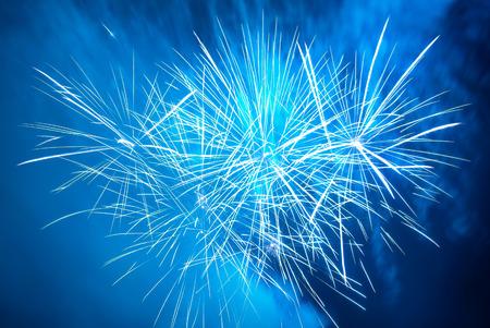 Photo pour Blue colorful fireworks on the black sky background. Holiday celebration. - image libre de droit