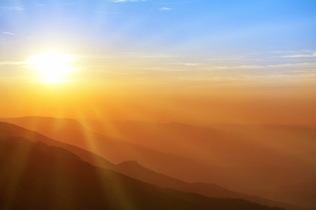 Foto de Beautiful sunset in the mountains. Colorful landscape with sun, sunrays and blue sky - Imagen libre de derechos