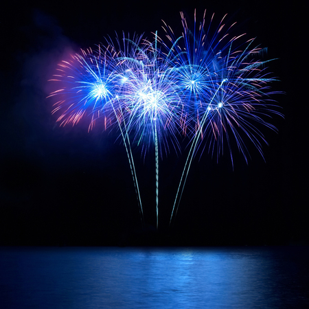 Photo for Blue fireworks above water with reflection on the black sky background - Royalty Free Image