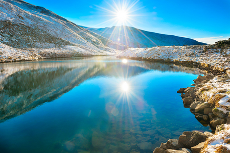 Photo for Beautiful blue lake in the mountains, morning sunrise time. Landscape with snow shining sun - Royalty Free Image