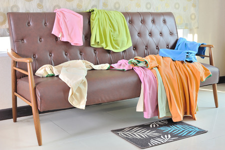 Photo for Messy clothes scattered on a sofa in living room - Royalty Free Image