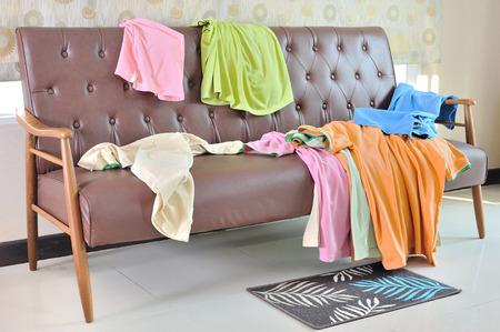 Foto de Messy clothes scattered on a sofa in living room - Imagen libre de derechos