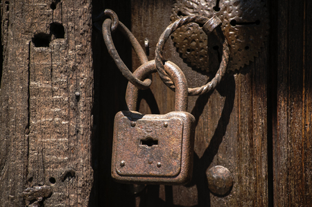 Foto de Old weathered grunge rusty locked padlock with rings on old wooden board door - Imagen libre de derechos