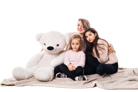 Mom and two daughters sit on the blanket and embrace, closing their eyes, and with them there is a teddy bear. Family isolated on white.