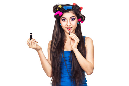 Foto de nice cheerful young girl in blue dress with hair curlers and with lipstick in her hand. woman paints her lips. isolated on white background - Imagen libre de derechos