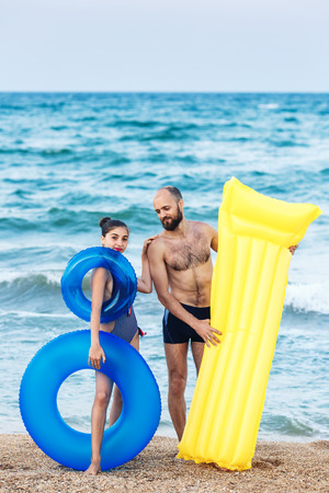 Photo for joyful father and daughter are standing on beach holding an inflatable mattress and circle - Royalty Free Image