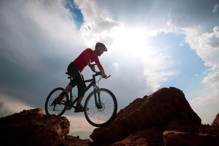 man mountain biking over extreme terrain