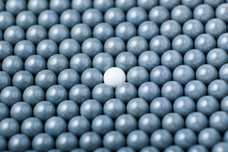 Photo pour White airsoft ball is among many black balls. Background of 6mm bbs. - image libre de droit