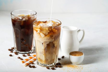 Foto für Ice coffee in a tall glass with cream poured over and coffee beans. Cold summer drink on a light blue background. - Lizenzfreies Bild