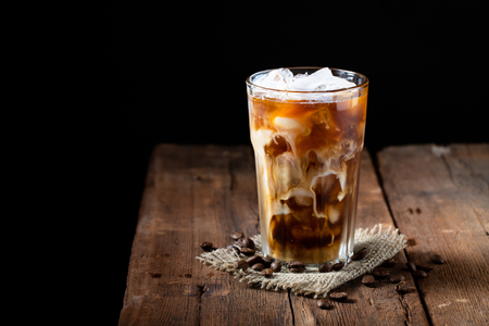 Photo pour Ice coffee in a tall glass with cream poured over and coffee beans on a old rustic wooden table. Cold summer drink on a dark wooden background with copy space. - image libre de droit