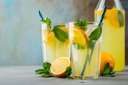 Foto de Two glass with lemonade or mojito cocktail with lemon and mint, cold refreshing drink or beverage with ice on rustic blue background. Copy space. - Imagen libre de derechos