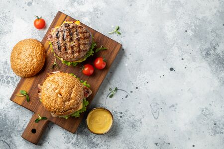 Photo pour Tasty grilled home made burger with beef, tomato, cheese, bacon and lettuce on a light stone background with copy space. Top view. fast food and junk food concept. Flat lay - image libre de droit